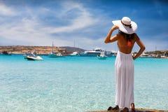La mujer elegante disfruta de la visión a las aguas claras de las islas de Koufonisia fotos de archivo libres de regalías