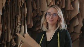 La mujer elegante elige un modelo de la plantilla para el vestido costura almacen de video