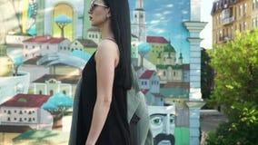 La mujer elegante en vestido negro y las gafas de sol caminan en la cámara lenta contra pintada