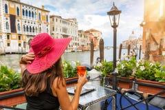 La mujer elegante goza de un aperitivo que se sienta al lado del Canale grande fotografía de archivo