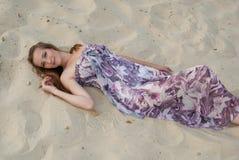 La mujer elegante hermosa miente en la arena Fotos de archivo libres de regalías