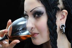La mujer elegante joven con los dreadlocks bebe el vino rojo Imagenes de archivo