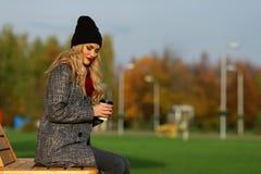 La mujer elegante joven sueña con café en un parque Fotografía de archivo libre de regalías