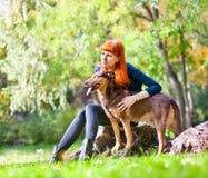 La mujer elegante se divierte con su perro grande en el parque Fotos de archivo