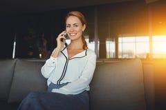 la mujer elegante sonriente que habla en el teléfono móvil durante resto en cafetería de lujo, copia área de espacio Fotos de archivo