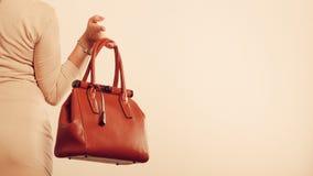 La mujer elegante sostiene el bolso marrón fotografía de archivo