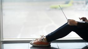 La mujer elegante y relajada se está sentando cerca de ventana y de la información que mecanografía en el ordenador portátil metrajes