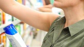 La mujer elige compras en las sustancias químicas de hogar de la tienda y los cosméticos 4k, a cámara lenta metrajes