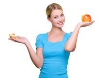 La mujer elige de la torta dulce y de la manzana roja Foto de archivo