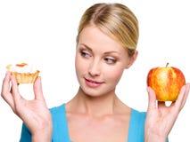 La mujer elige de la torta dulce y de la manzana roja Foto de archivo libre de regalías