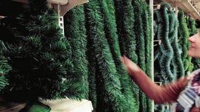 La mujer elige la decoración de la Navidad almacen de video