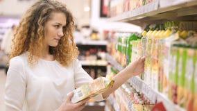 La mujer elige el jugo en el supermercado El hacer compras en la tienda metrajes