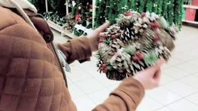 La mujer elige la guirnalda de la Navidad almacen de metraje de vídeo