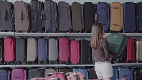 La mujer elige la maleta en el departamento almacen de video