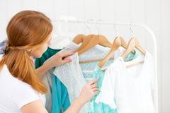 La mujer elige la ropa en su guardarropa Imagenes de archivo
