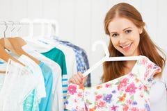 La mujer elige la ropa en su guardarropa Foto de archivo