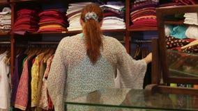 La mujer elige la ropa en una tienda metrajes