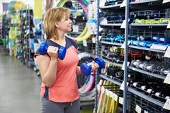La mujer elige las pesas de gimnasia para la aptitud en tienda de los deportes Imagen de archivo