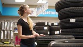 La mujer elige los neumáticos para el coche almacen de metraje de vídeo