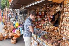 La mujer elige los recuerdos hechos a mano rusos en la tienda de regalos Imagenes de archivo