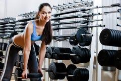 La mujer elige pesas de gimnasia Imagenes de archivo