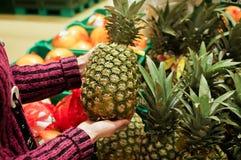 La mujer elige la piña en un supermercado Copie el espacio fotografía de archivo