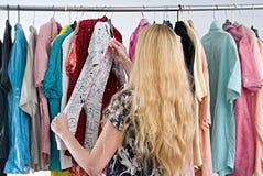 La mujer elige la ropa en el armario del guardarropa fotografía de archivo libre de regalías