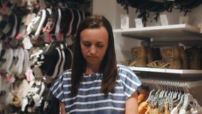 La mujer elige la ropa en la tienda almacen de metraje de vídeo