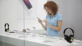 La mujer elige smartphone en una tienda almacen de metraje de vídeo