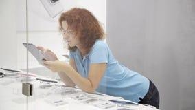 La mujer elige smartphone en una tienda almacen de video