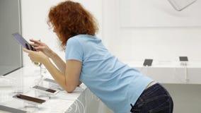 La mujer elige smartphone en una tienda metrajes
