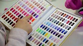 La mujer elige un color para los clavos de pintura en un salón de belleza Una colección de probadores del esmalte de uñas en dive metrajes