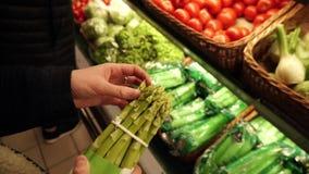 La mujer elige un manojo de espárrago orgánico fresco en el supermercado local metrajes