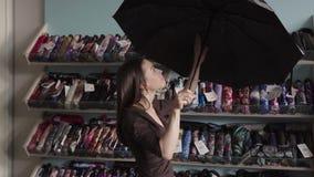 La mujer elige un paraguas en tienda almacen de video
