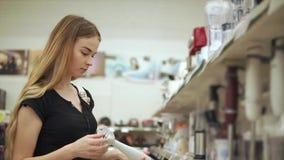 La mujer elige una licuadora en la tienda almacen de metraje de vídeo