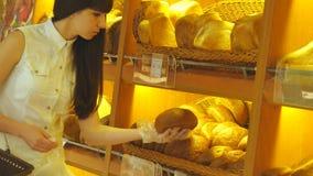 La mujer elige y poniendo un pan del pan fresco en un paquete en el supermercado Chica joven que toma una barra de pan de almacen de video