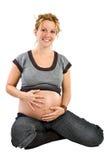 La mujer embarazada agradable que sonríe y acaricia su panza Imágenes de archivo libres de regalías