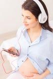 La mujer embarazada alegre es relajante con melodía Imágenes de archivo libres de regalías