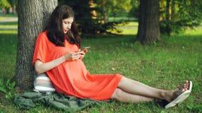 La mujer embarazada atractiva en ropa informal está utilizando el smartphone que se sienta en hierba debajo de árbol en parque Em metrajes