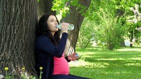 La mujer embarazada bebe el agua de la botella almacen de video