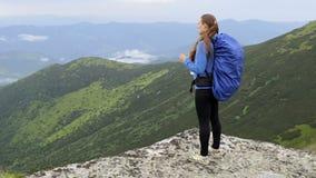 La mujer embarazada bebe el agua en la montaña almacen de metraje de vídeo