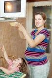 La mujer embarazada calienta el alimento fotos de archivo libres de regalías