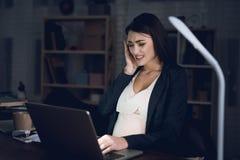 La mujer embarazada cansada joven trabaja en casa solamente La mujer embarazada experimenta dolor de cabeza imágenes de archivo libres de regalías