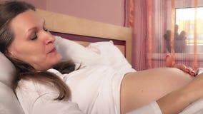 La mujer embarazada cariñosa acaricia su vientre que miente en la cama blanca almacen de metraje de vídeo