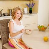 La mujer embarazada come la sopa Imagen de archivo libre de regalías