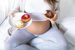 La mujer embarazada come un buñuelo sabroso fotografía de archivo libre de regalías
