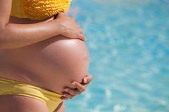 La mujer embarazada con entrega la panza Foto de archivo libre de regalías