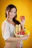 La mujer embarazada con la manzana y la cesta de mimbre cosechan Fotografía de archivo