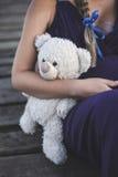 La mujer embarazada con las manos y tiene muñeca del oso Imagenes de archivo