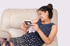 La mujer embarazada con ultrasonido del control de la mano de los zapatos de bebé y la juega Fotografía de archivo libre de regalías